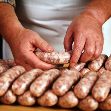 Close up of hands processing sausages